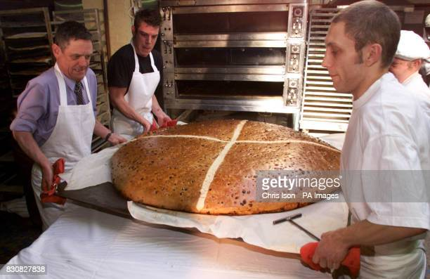 Four bakers struggle to carry a huge hot cross bun from the oven at Pegrum's Bakery in Rustington East Sussex in their attempt to beark the record...