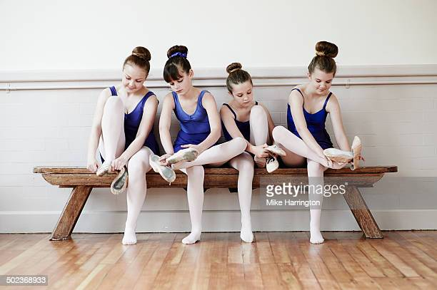 Four ballet dancers putting on ballet shoes