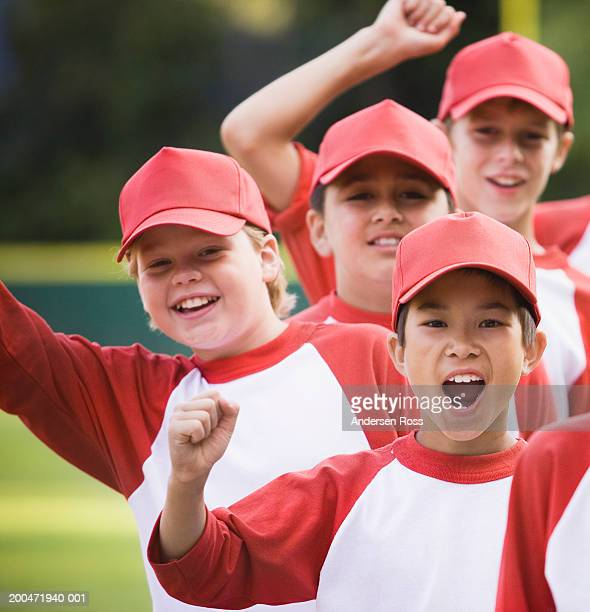 Four baseball players (9-11) cheering, portrait