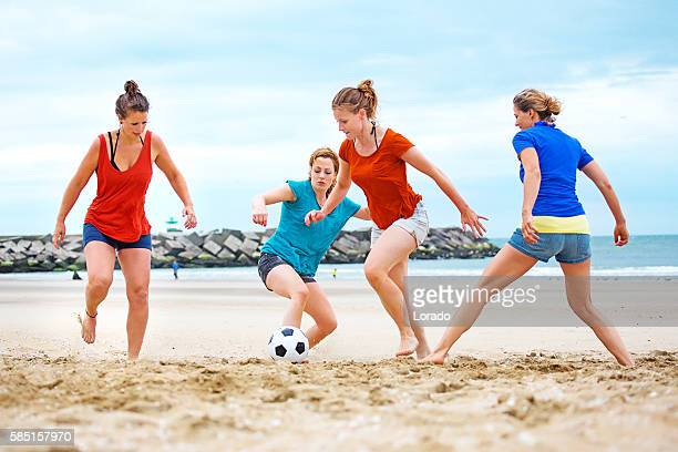 Four beautiful female friends playing beach soccer in Summer