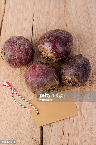 Four beetroots and blank label on wood