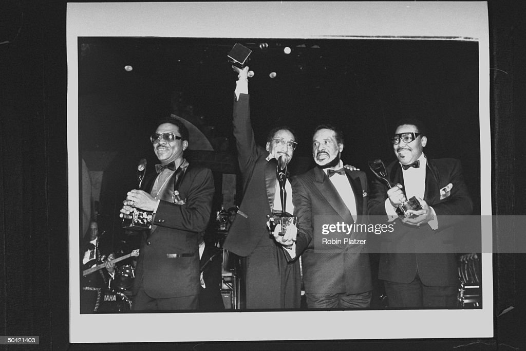 Four black members of the vocal group The Four Tops incl. Levi Stubbs (2R), Duke Fakir, Obie Benson & Lawrence Payten, holding their awards as they pose together on stage at Rock & Roll Hall of Fame induction ceremony at the Waldorf-Astoria hotel.