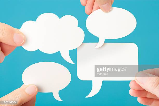 Four blank white conversation speech bubbles