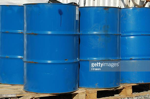 Four blue industrial-sized chemical barrels