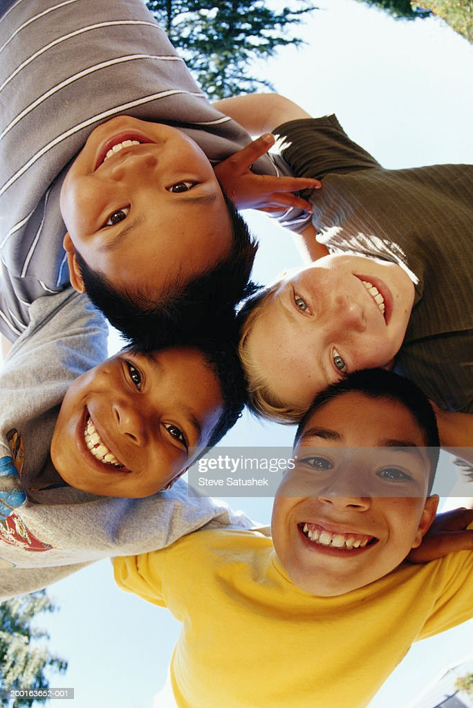 Four boys (8-11) forming a circle, view from below : Stock Photo