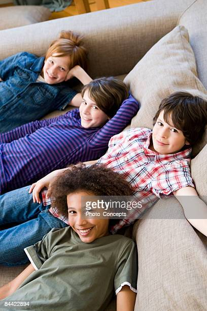 Four boys hanging round on a couch