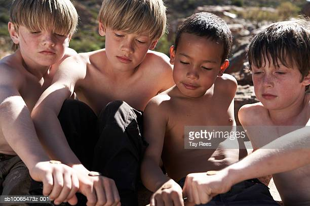 Four boys (6-13) holding stones on wrist, close-up