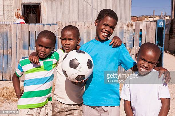 Four boys in the township with a soccer ball, Cape Town, South Africa