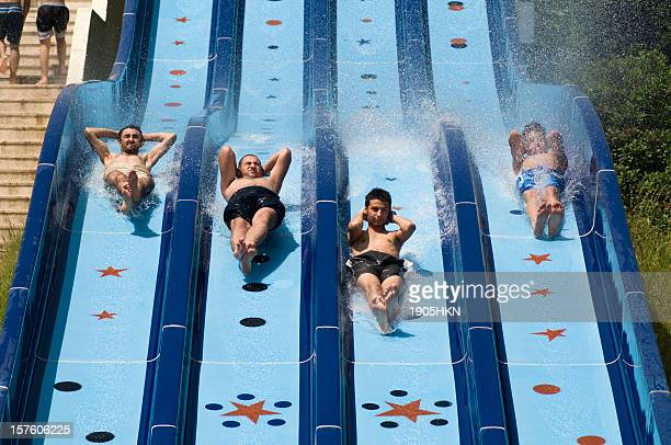 Four boys racing down the water slide