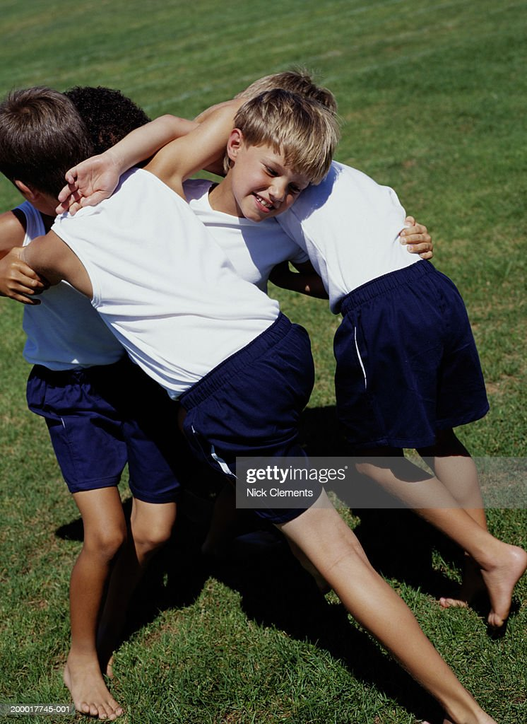 Images Of Boys Painted Bedrooms: Four Boys Wrestling In Sports Field Stock Photo