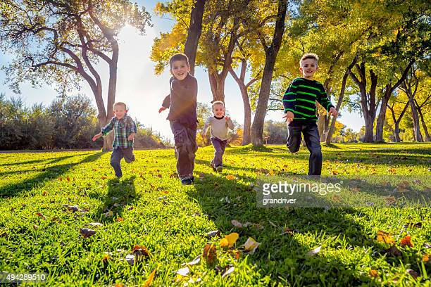 Four Brothers Running in a park in the Autumn