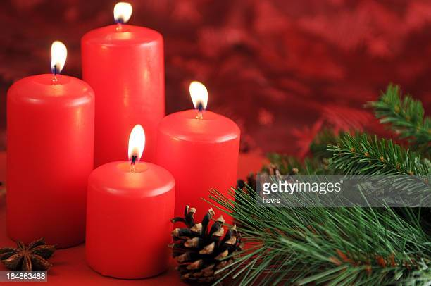 four burning Advent candles with pine twig and cone