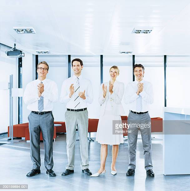 Four business colleagues applauding in office, portrait