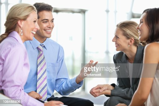 Four business executives laughing in a meeting at office : Stock Photo