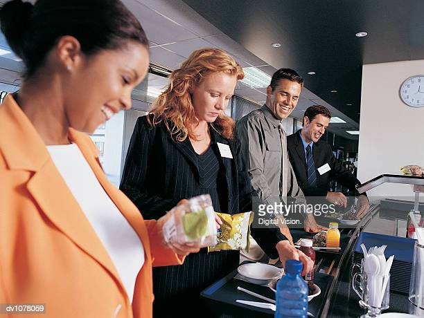 Four Business Executives Standing in a Line in a Canteen