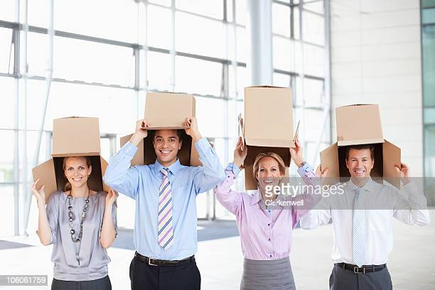 Four business executives with empty cardboard boxes standing in row at new office
