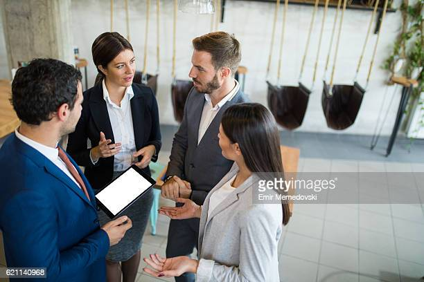 Four business people discussing business strategy using digital tablet