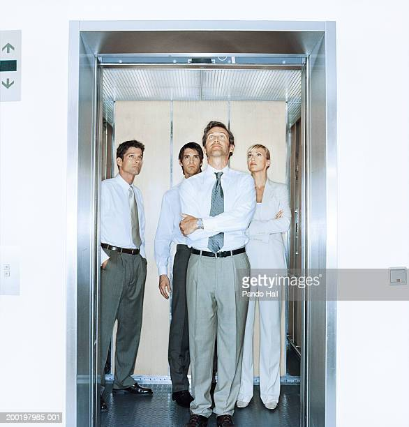 Four business people in lift, two with arms folded, looking up