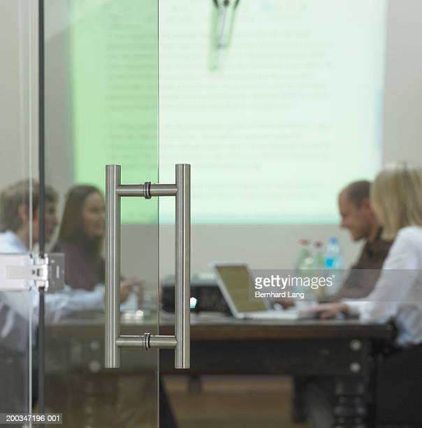 Four business people in meeting, view through doorway