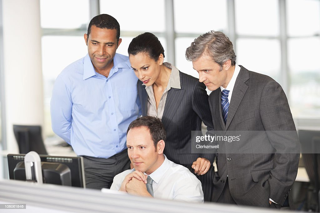 Four business people looking at computer monitor : Stock Photo