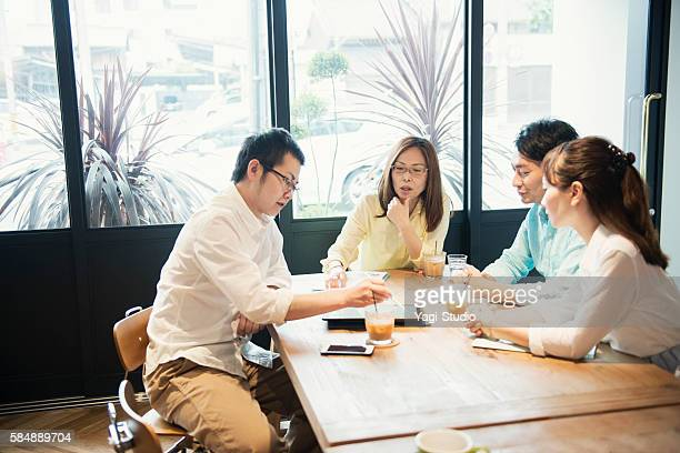 Four business people meeting in a cafe