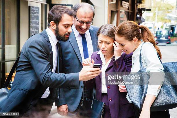Four business people react to media shown on mobile phone