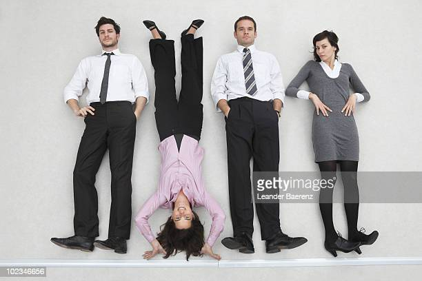 Businesspeople lying side by side, woman doing handstand, portrait