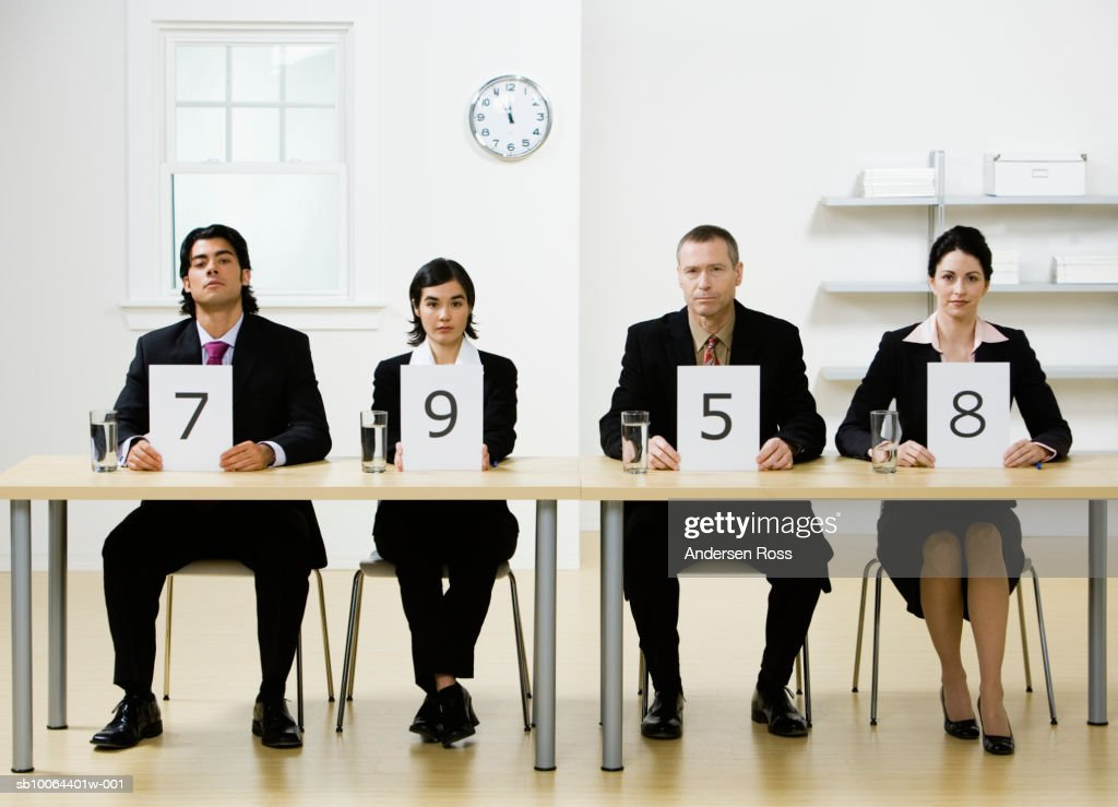 Four business people sitting at desk, holding score cards, portrait