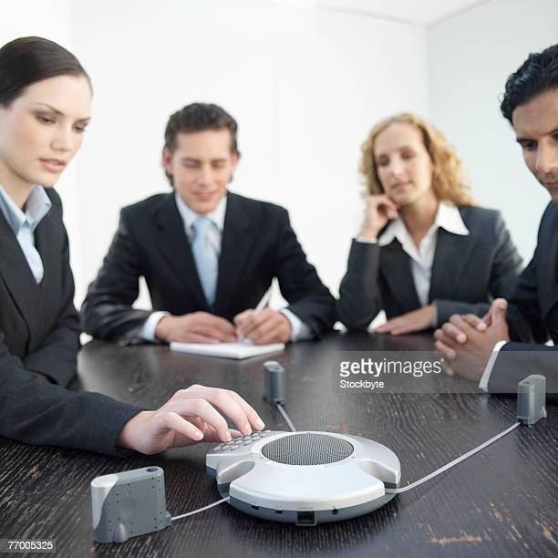 Four business people sitting at desk using conference phone, woman pushing button, focus on foreground