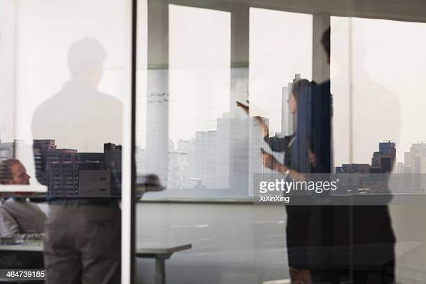 Four business people standing and looking at a white board on the other side of a glass wall