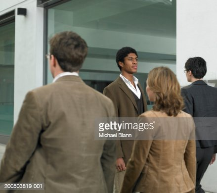 Four business people walking on sidewalk outside office building : Stock Photo