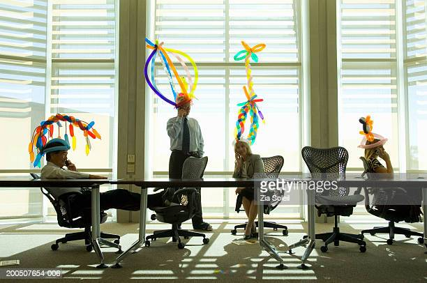 Four business people wearing balloon hats in meeting room