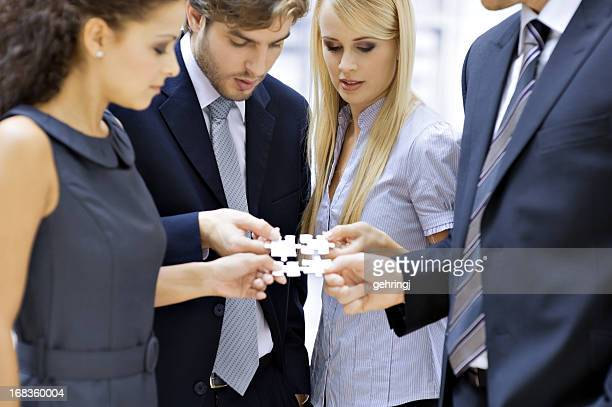 Four business people with puzzle
