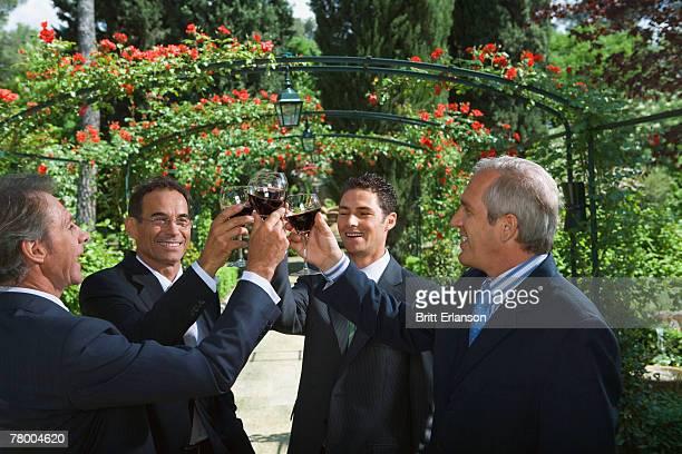 Four businessmen drinking wine in a garden