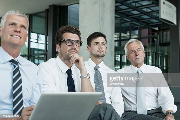 Four businessmen sitting with laptop