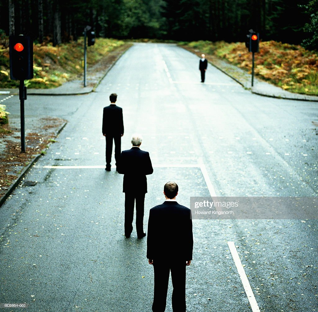 Four businessmen standing at red traffic lights : Stock Photo
