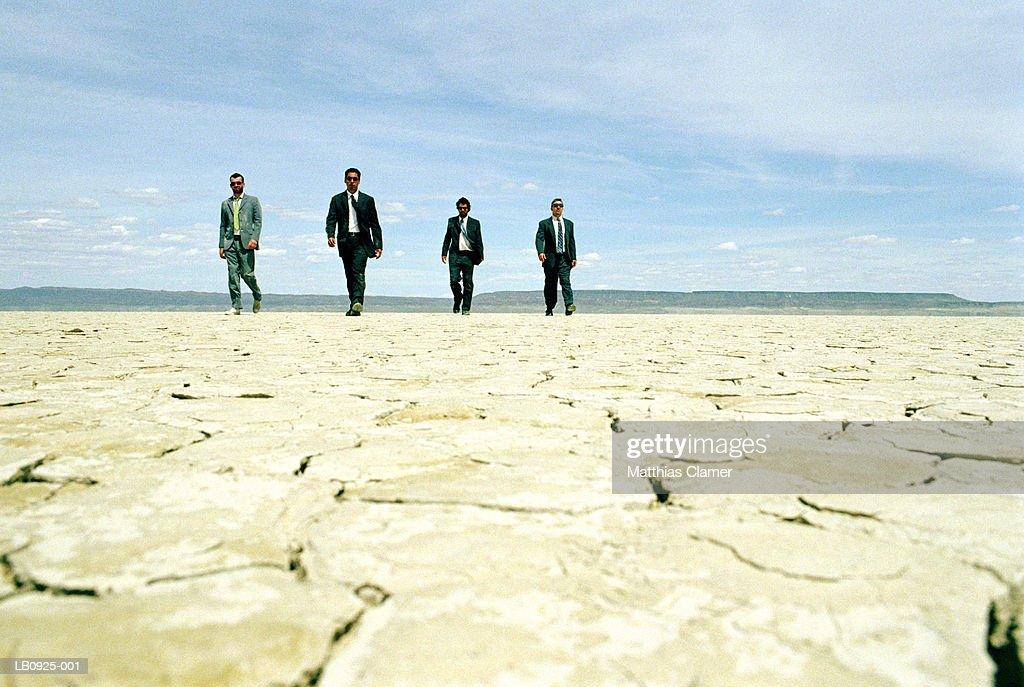 Four businessmen walking in desert : Stock Photo