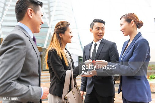Four Businessmen with Business Cards, Hong Kong, China, Asia