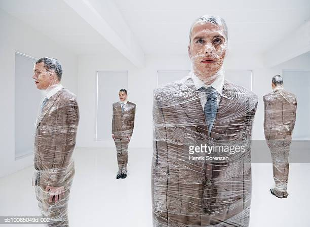 Four businessmen wrapped in plastic wrap (digital composite)