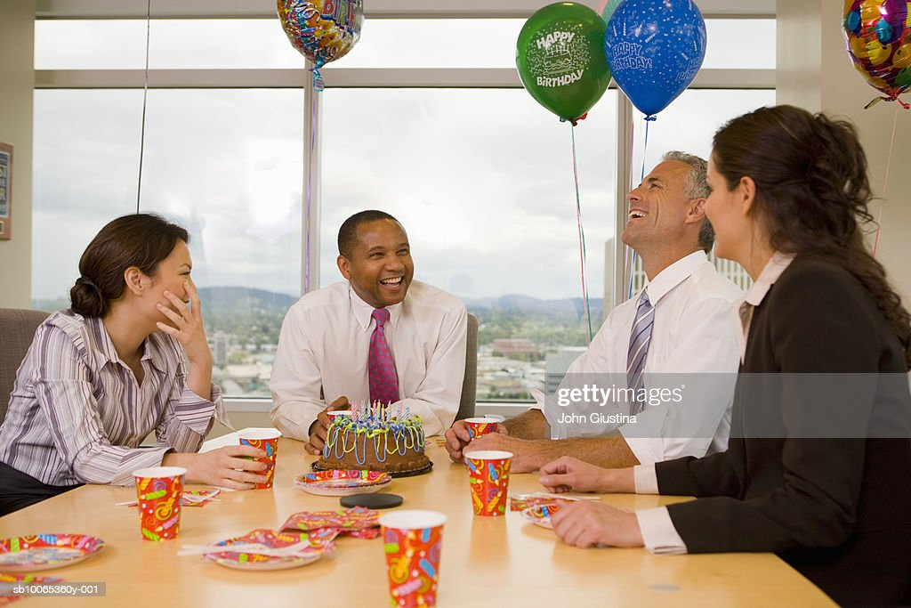 Four businesspeople celebrating birthday, laughing : Stock Photo