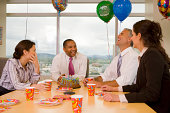 Four businesspeople celebrating birthday, laughing