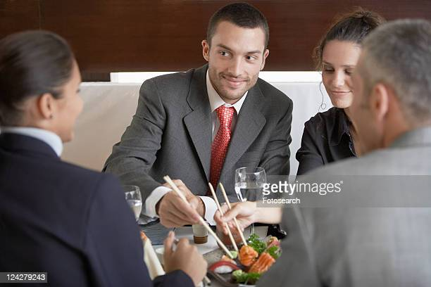 Four businesspeople having lunch in sushi restaurant
