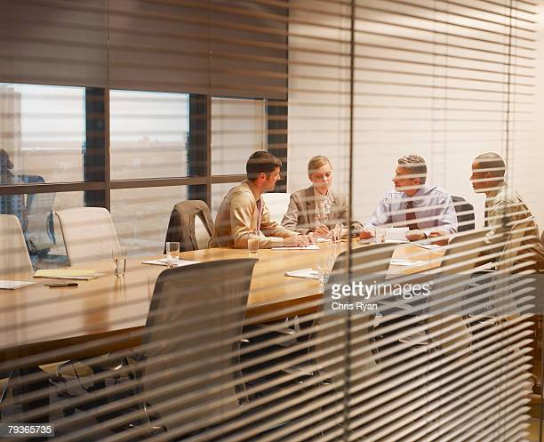 Four businesspeople in a boardroom through a window