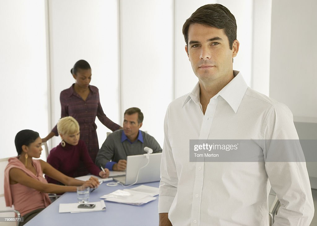 Four businesspeople in a boardroom with a laptop with a businessman in foreground : Stock Photo