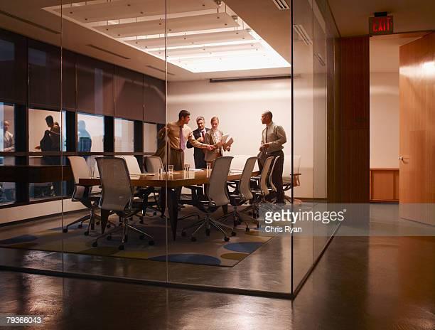 Quatre hommes d'affaires dans la salle de conseil vous préparer à sortir