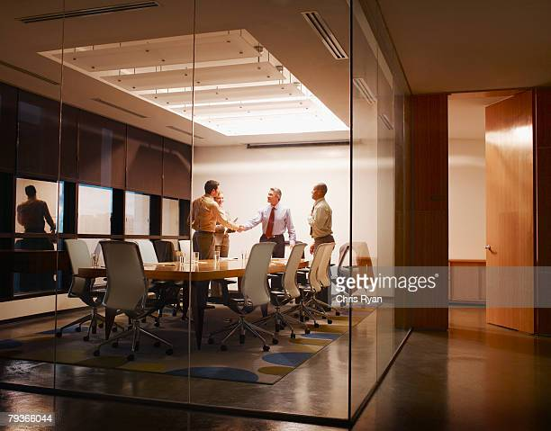 Four businesspeople in boardroom with two shaking hands