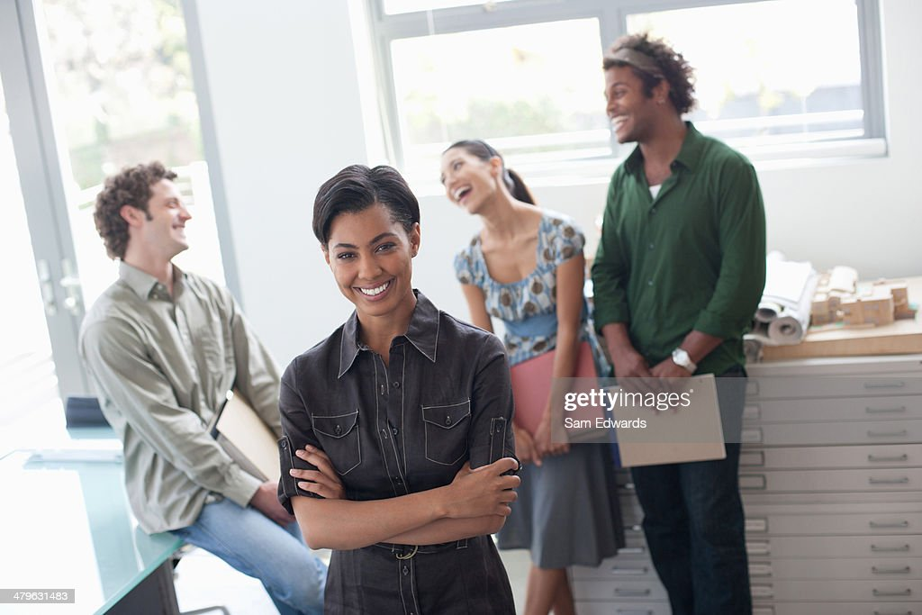 Four businesspeople in office smiling : Stock Photo
