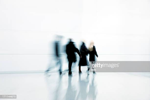 Four Businesspeople Walking in White Corridor, Blurred Motion