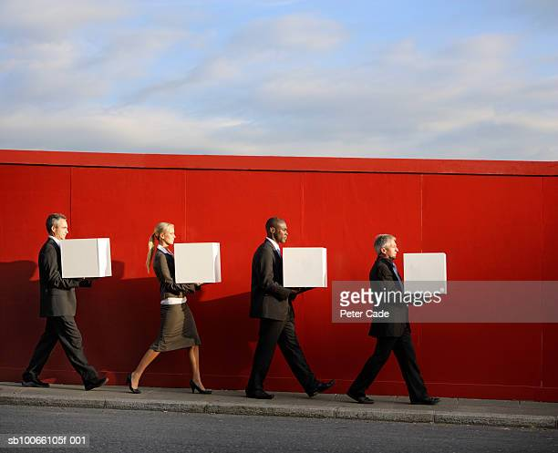 Four businesspeople walking with holding white boxes in front of red wall, side view