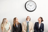 Four businesspeople sitting on bench and looking up at clock. Horizontally framed shot.